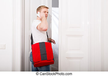 Leaving - A young and busy student coming home while talking...