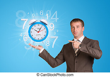 Businessman hold alarm clock with figures - Businessman in a...