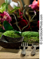 Nature themed dinner table setting with plants as...