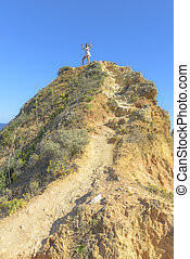 Young girl standing on top of a cliff