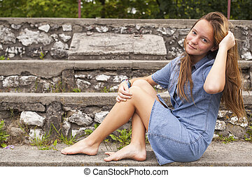 Beautiful young girl sitting in the park.