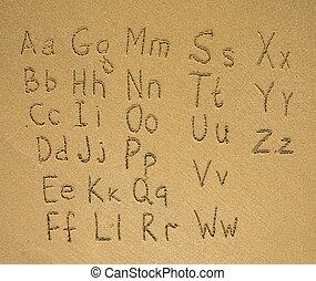 Alphabet written on a wet beach sand.