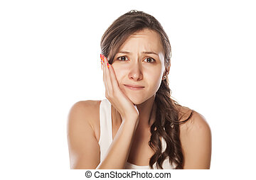 jaw pain - sad young woman holding her hand on her jaw