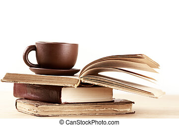 Stack of books and cup on wooden table. Shallow DOF.