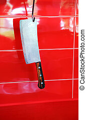 meat cutter - cutter for meat hangs suspended on a red wall...