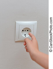 Child sticks his fingers in the socket. Dangerous situation...