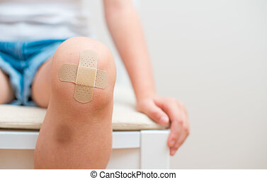 Child knee with an adhesive bandage and bruise