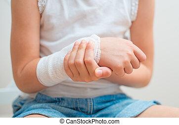 Child arm with gauze bandage on it.