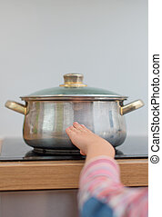 Child touches hot pan on the stove Dangerous situation at...
