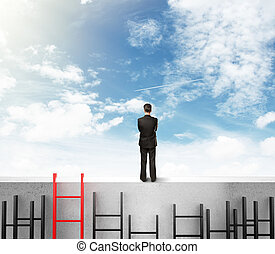 businessman  on wall - businessman in suit standing on wall