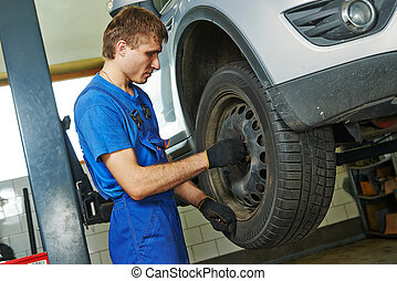 auto mechanic screwing car wheel