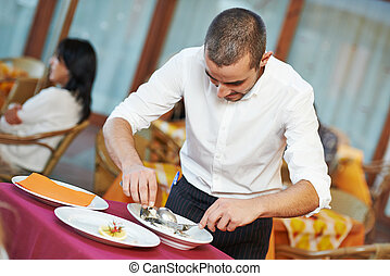 waiter man dressing fish at restaurant - young male waiter...