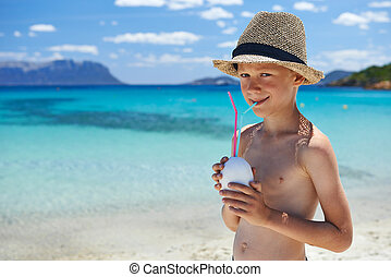 Boy with coconut on turquoise beach
