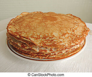 Pancakes. - The appetizing toasted pancakes lie on a dish....
