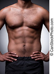 Perfect male body. Close-up of shirtless African man holding...