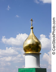 Gold plated dome with a cross on the sky background