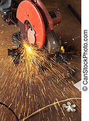 Worker cutting metal and spark