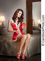 Young sexy Santa holding a gift, boudoir shoot. Attractive...