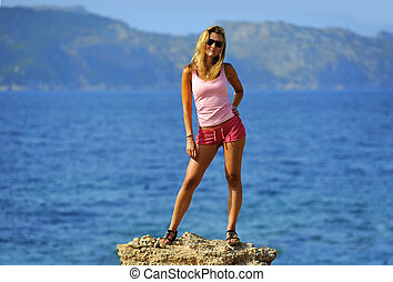 attractive woman standing at rock feeling free in front of the sea