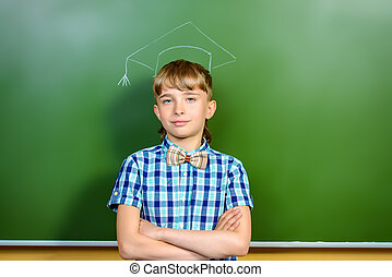 diligent - Smart schoolboy stands at the blackboard in the...