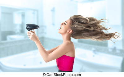 Woman drying hair - Young blonde woman drying her long hair...