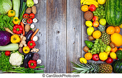 Huge group of fresh vegetables and fruit on wooden background -
