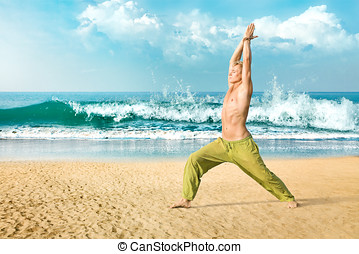 Man meditating in warrior pose - Young man doing yoga and...