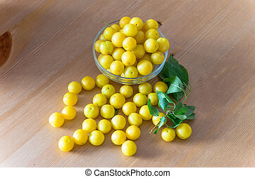 pile of yellow mirabelle plums on wooden table