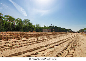 Road construction - Bulldozers traces on the sand during the...