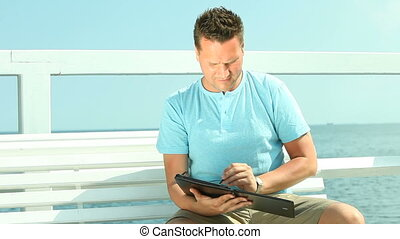 Man using tablet by sea