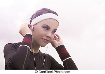 Portrait of Fitness Caucasian Woman Listening to Music...