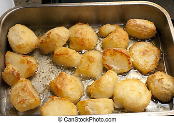 Delicious golden crispy roast potatoes in a baking tray...