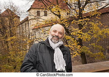A middle-aged man smiling on a background of autumn trees in...