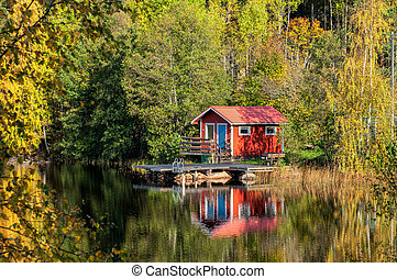 Autumn in Sweden - Traditional red little summer cottage at...
