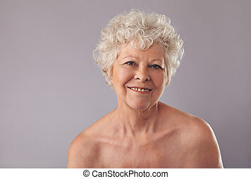Senior woman smiling on grey background - Closeup of an...