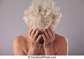 Sad senior woman on grey background - Portrait of unhappy...