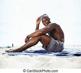 Handsome young man sitting on beach - Portrait of handsome...
