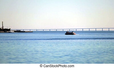 Ferry Crosses the Bay to the background Bridge - Ferry...
