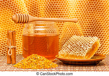 Honey in jar with dipper, honeycomb, pollen and cinnamon on...