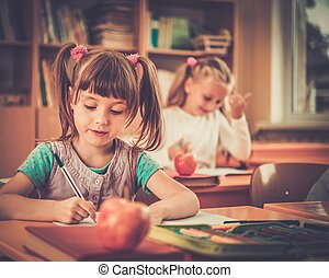 Little schoolgirl sitting behind school desk during lesson...