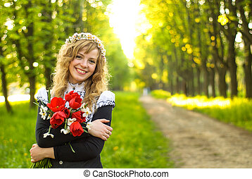 Girl is walking in the park Cute woman with flowers