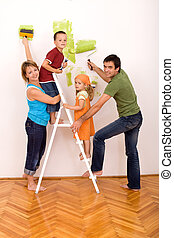 Happy family with painting utensils repainting their home -...
