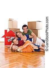 Happy family laying on the floor of their new home - Happy...