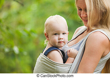 Baby in sling - Mother is carrying her child and walking....