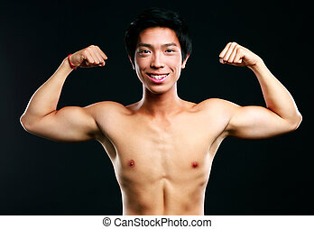 Happy asian muscular man with his arms stretched out on...