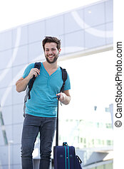 Happy young man standing outside with bags