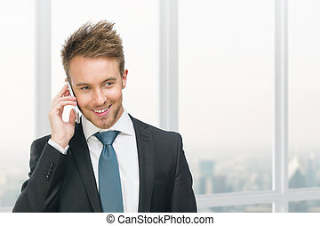 Businessman speaking on cell phone against window -...