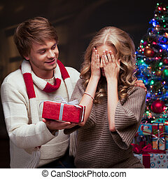 young couple presenting christmas gift - young happy smiling...