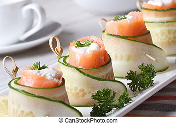 salmon rolls with cucumber, cream cheese and herbs closeup...