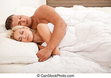 Young couple sleeping and hugging on bed